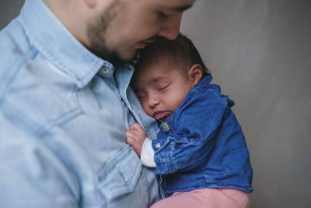 bébé qui dort dans les bras de papa