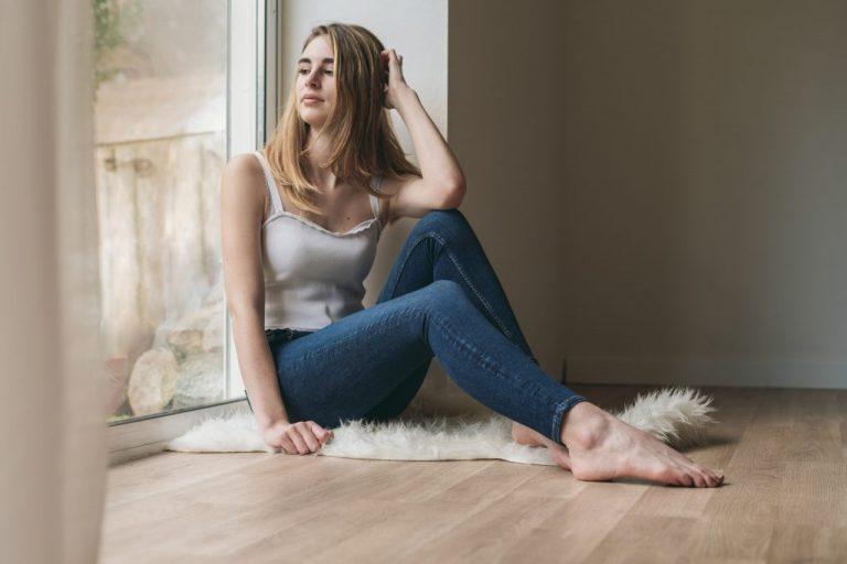 jeune fille assise près d'une fenêtre