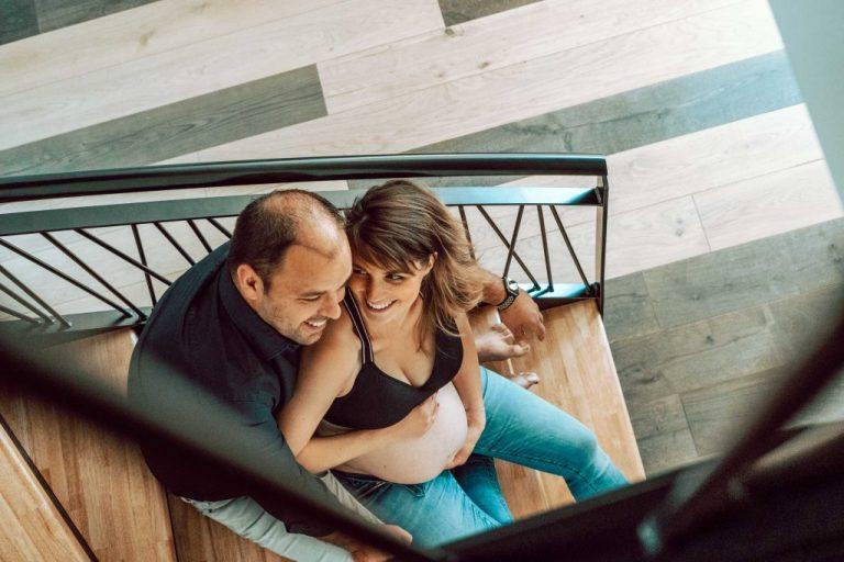 couple heureux assis dans l'escalier en bois avec une femme enceinte